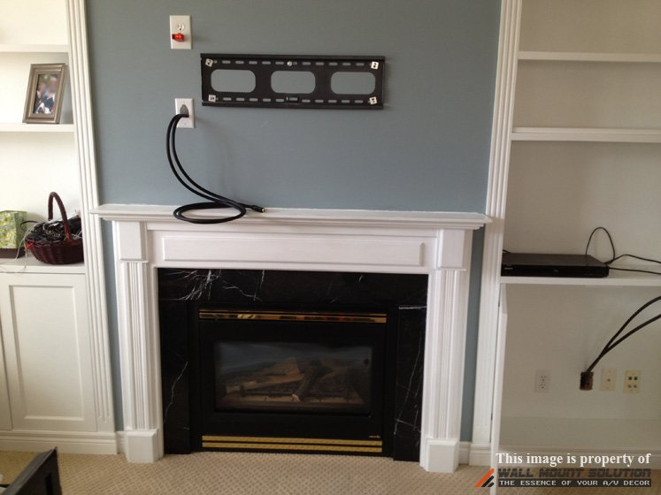 TV wall mount installation with wire concealment over fireplace